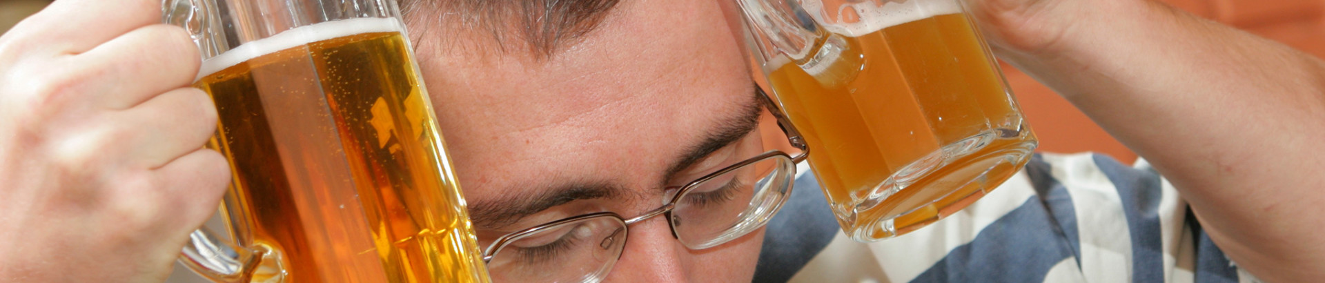 guy-with-hangover-cooling-his-head-with-two-beers-IST